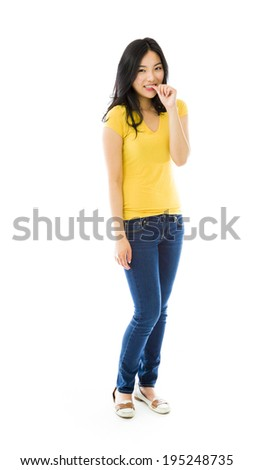 Young Asian woman smiling with finger in mouth - stock photo