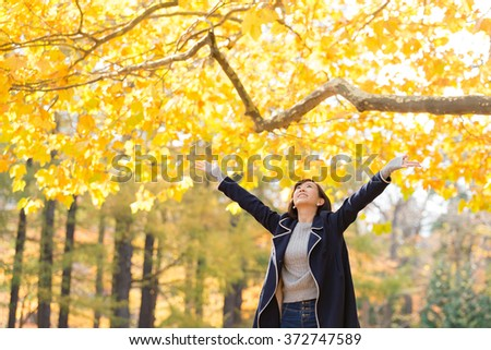Young Asian woman spreading arms under the Autumn tree. - stock photo