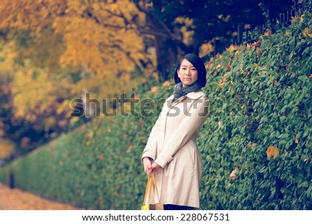 Young Asian woman standing on sidewalk.(retro effect) - stock photo