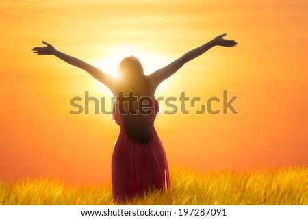 Young asian woman standing open her arms under the sunrise - stock photo