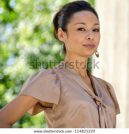 Young Asian Woman Stands Confidently Near Memorial