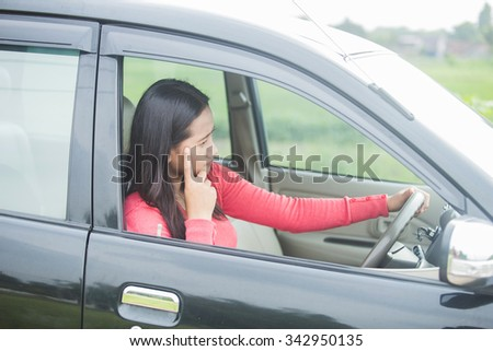 Young Asian woman stress while driving her car - stock photo