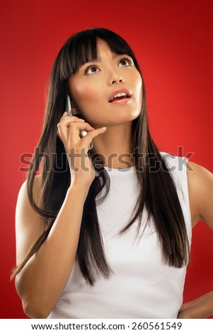 Young Asian woman talking on phone. - stock photo
