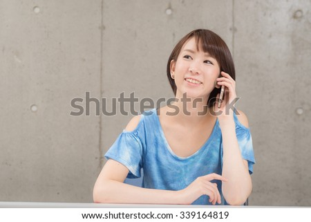 Young Asian woman talking with a smart phone. - stock photo