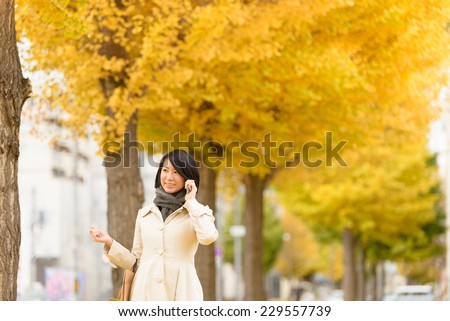 Young Asian woman talking with smart phone under the ginkgo trees. - stock photo