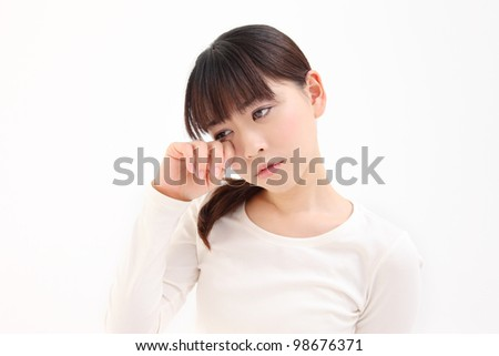 Young Asian woman touch the eye white background - stock photo
