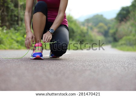 young asian woman tying shoelace