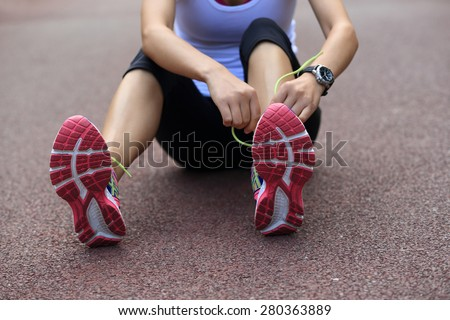 young asian woman tying shoelace on fossil forest trail - stock photo