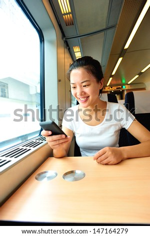 young asian woman use smartphone interior of train/subway - stock photo