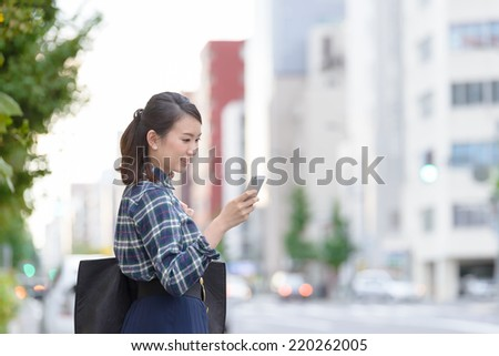 Young Asian woman using a smart phone on a city corner. - stock photo