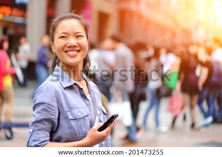 young asian woman using her smart phone on shopping street