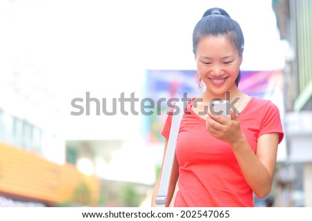 young asian woman using her smart phone on shopping street - stock photo