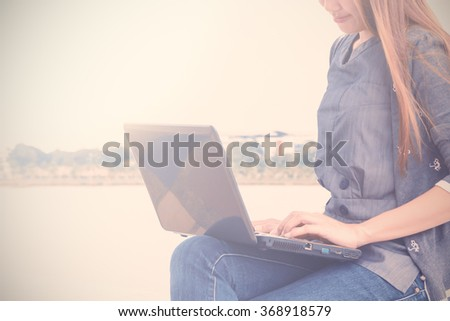 Young asian woman using laptop at outdoors. Soft focused.