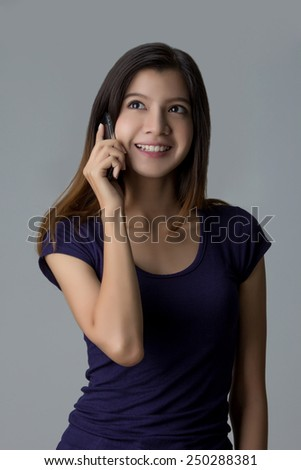 Young Asian woman using mobile phone on isolated background