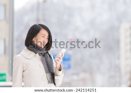 Young Asian woman using smart phone in a winter city. - stock photo