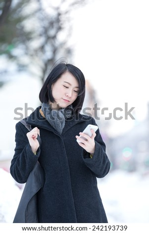 Young Asian woman using smart phone on a winter city.