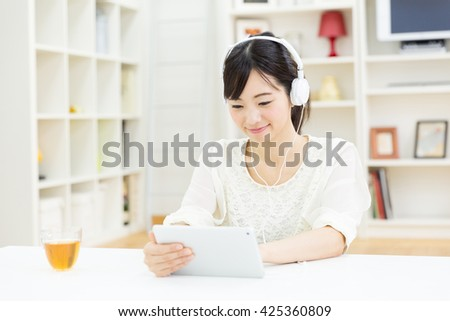 young asian woman using tablet computer in the room - stock photo