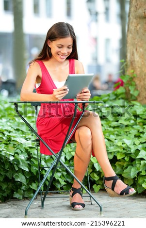Young asian woman using tablet pc in Bryant Park, Manhattan, New York City. Young casual woman using tablet computer app and 4g network - stock photo