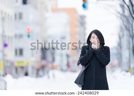 Young Asian woman warming her hand. - stock photo