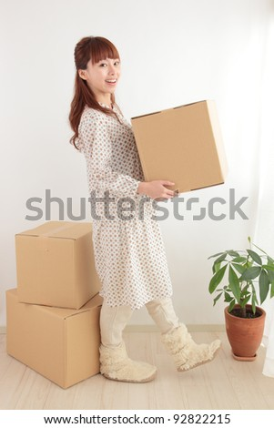 Young Asian woman with a cardboard box - stock photo