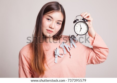 Young Asian woman with a clock on gray background