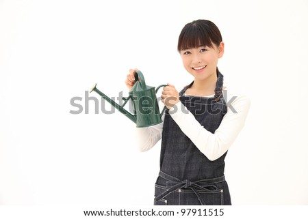 Young Asian woman with a Watering Can on a white background - stock photo
