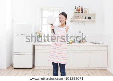 Young Asian woman with cooking utensils in the kitchen - stock photo