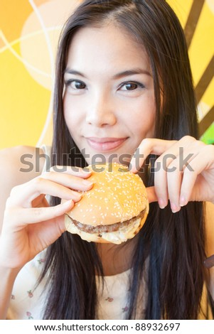 Young asian woman with her burger in fastfood restaurant - stock photo