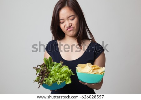 Young Asian woman with potato chips and salad on gray background