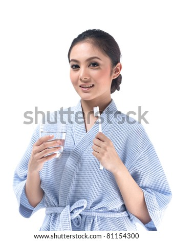 Young asian woman with toothbrush and a glass of water - stock photo