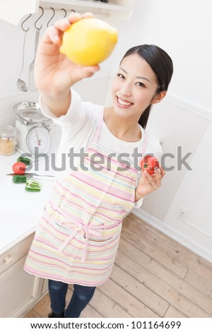 Young Asian woman with vegetables in the kitchen - stock photo