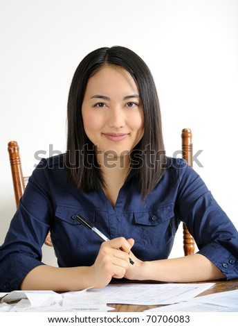 Young Asian woman working on her US Income Tax return for the IRS - seated at a table with papers spread out in front of her - smiling