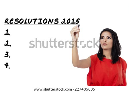 Young asian woman writes her resolutions list in 2015, isolated over white background - stock photo