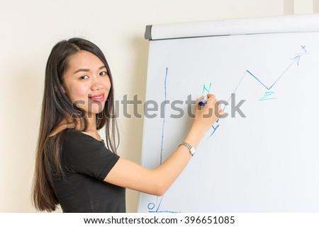 Young asian woman writing on a flipchart - stock photo