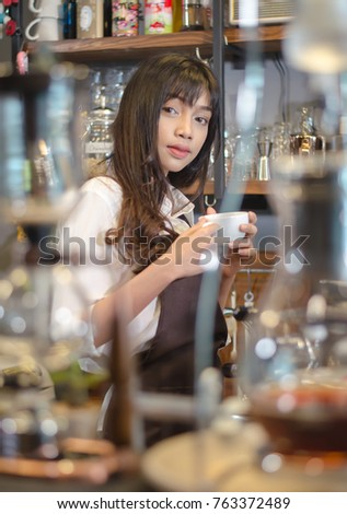 Young asian women barista hold coffee cup serving a client at the coffee shop,start up small business owner food and drink concept.