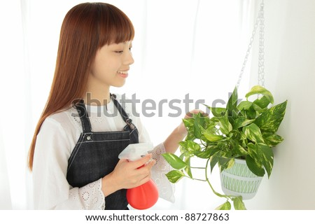 Young Asian women raise the water to plants - stock photo