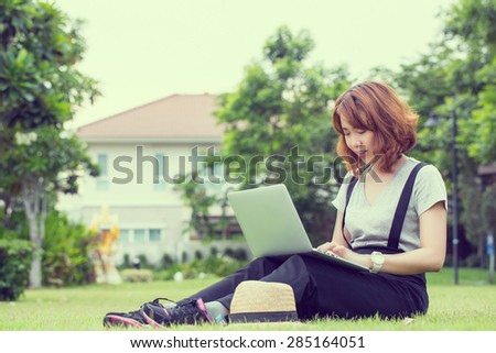 Young Asian women use labtop computer for search information in the garden.