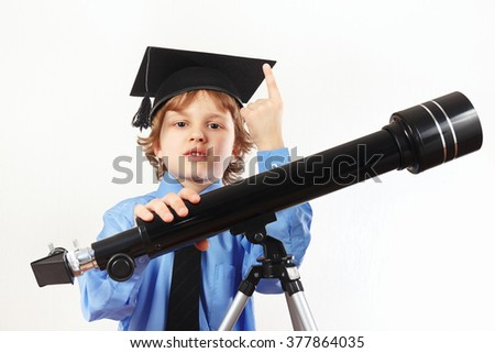 Young astronomer in academic hat with telescope on a white background - stock photo