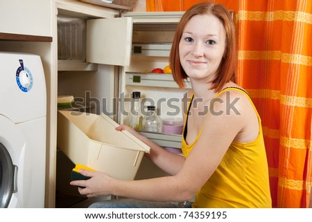 Young at her kitchen - stock photo