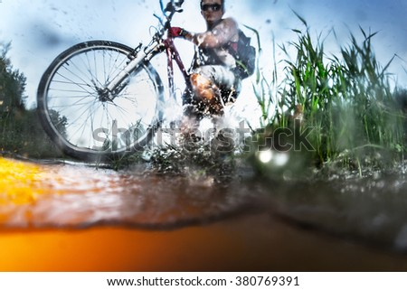 Young athlete crossing the river with bicycle. Focus on the wheel and grass