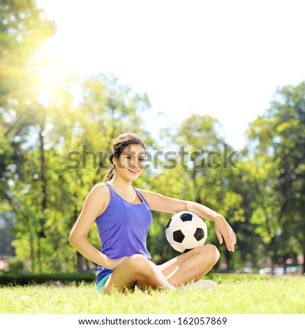 Young athlete female sitting on a green grass and holding a soccer ball in a park, shot with a tilt and shift lens - stock photo