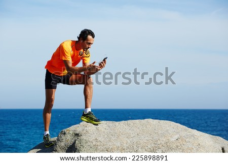 Young athlete in bright sportswear holding mobile smart phone standing on sea background at sunny day, athletic fit man using mobile phone listening to music during workout training outdoors - stock photo