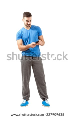 Young athlete in sport outfit using smart phone. Full body length portrait isolated over white background. - stock photo