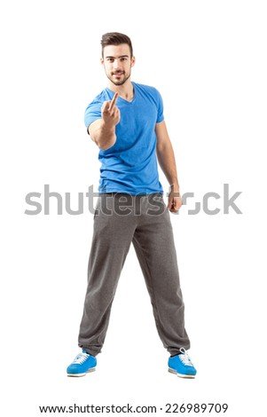 Young athlete in sportswear showing middle finger angry gesture. Full body length isolated over white background. - stock photo