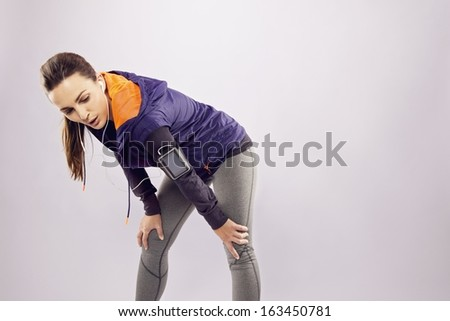 Young athlete in sportswear with hands on her knees. Beautiful woman resting after jogging over grey background - stock photo