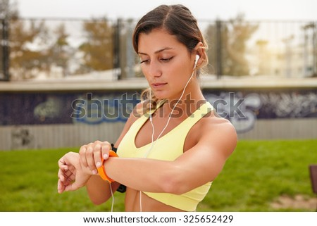 Young athlete in tank top looking at smart watch outdoors - stock photo