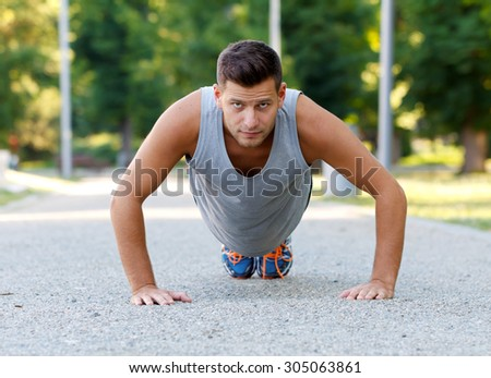 Young athlete male doing push ups outdoor - stock photo