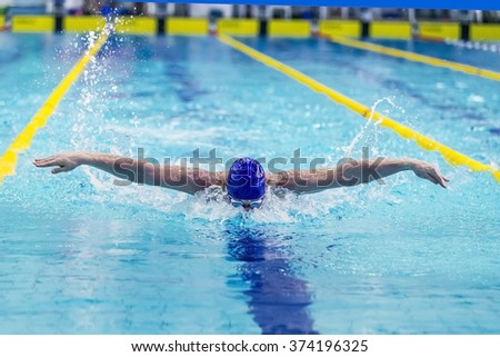 young athlete male swimmer swimming in pool butterfly. front view - stock photo