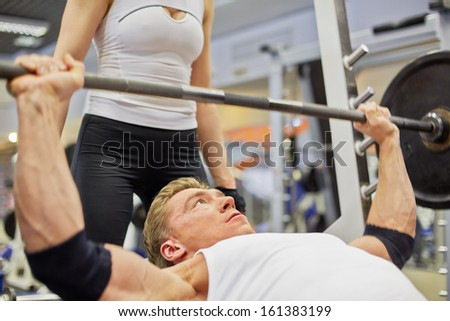 Young athlete man does bench press from chest exercise in gym hall under supervision of female coach