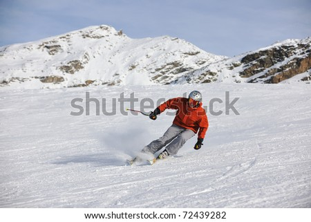 young athlete man have fun during skiing sport on hi mountain slopes at winter seasson and sunny day - stock photo